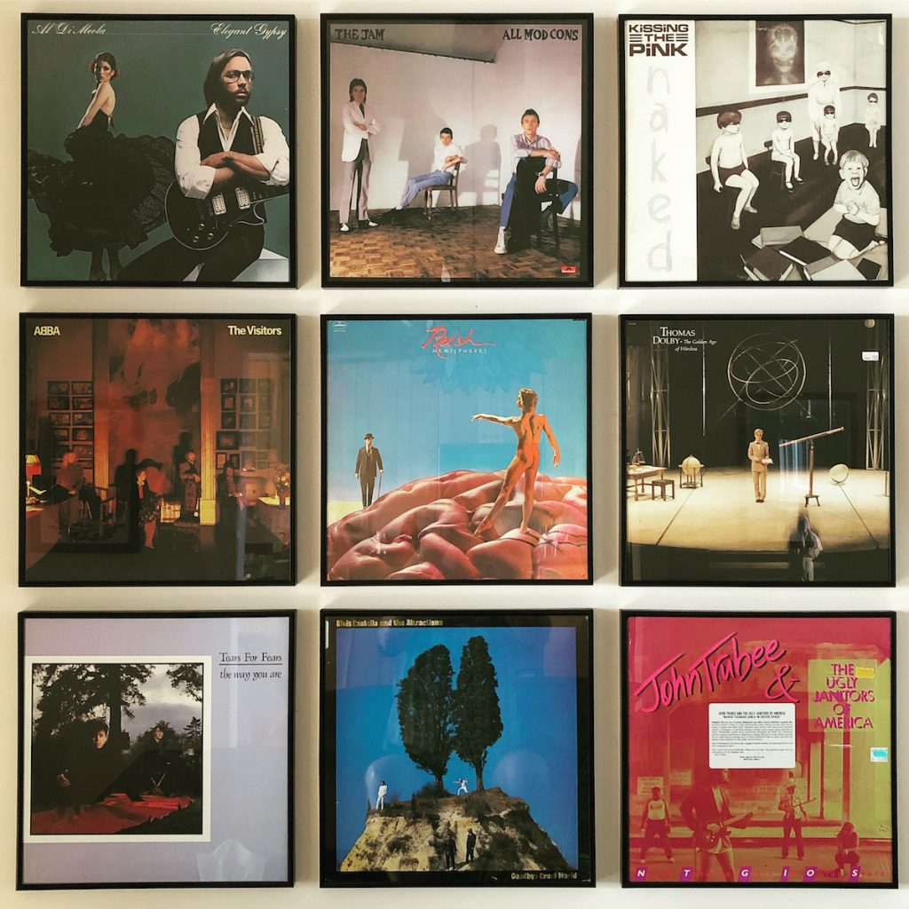 An arrangement of nine LP record covers on a wall, in which all the pictured figures are maintaining distance from one another. Artists include Al diMeola, The Jam, Kissing the Pink, Abba, Rush, Thomas Dolby, Tears for Fears, Elvis Costello & the Attractions, and John Trubee & the Ugly Janitors of America